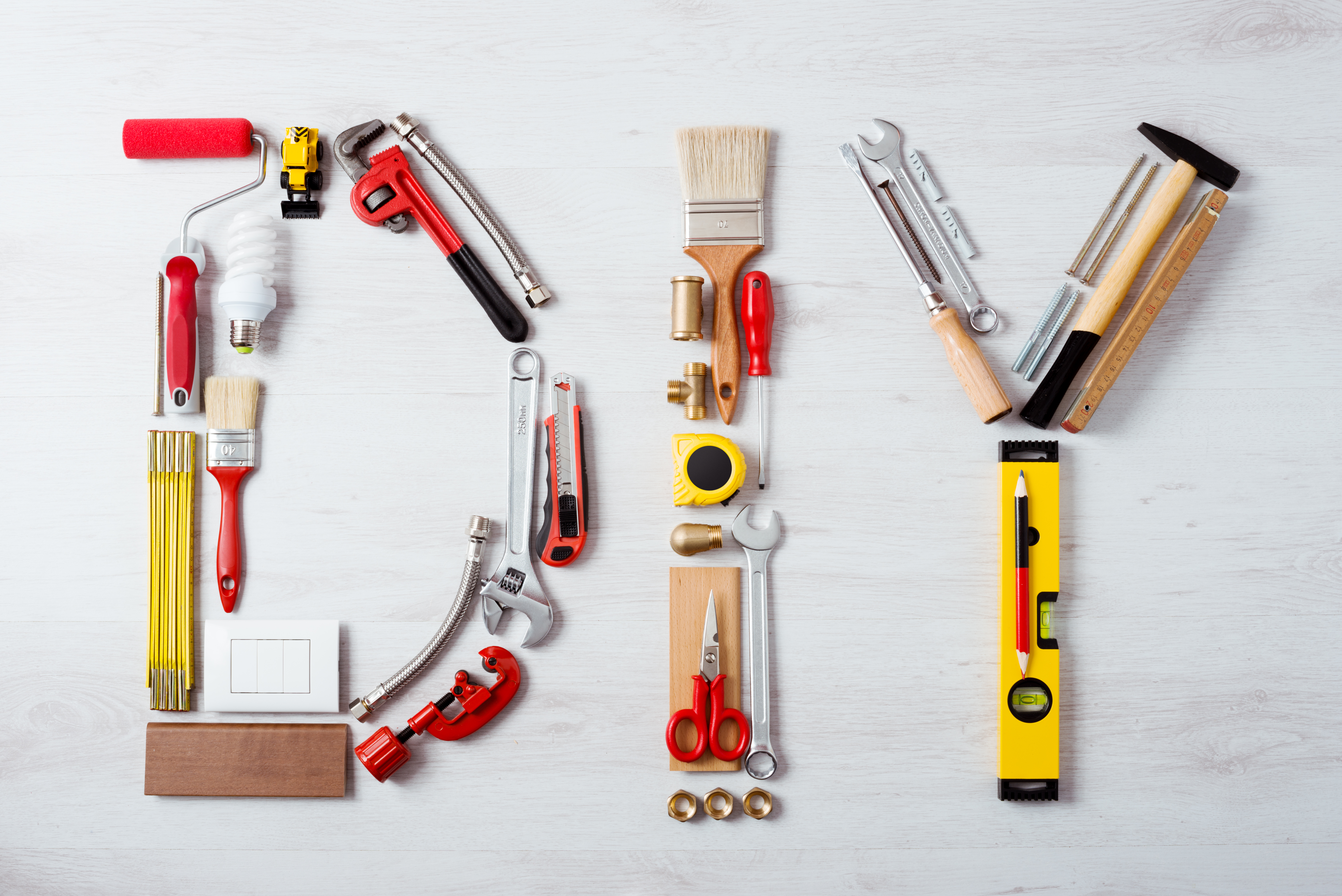 Construction tools in the form of house on wooden background. construction tools: pliers, hammer, pruner, screws, putty knife and ruler