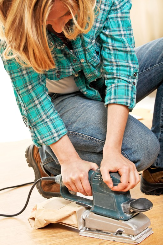 Man using an electric sander on wood floor