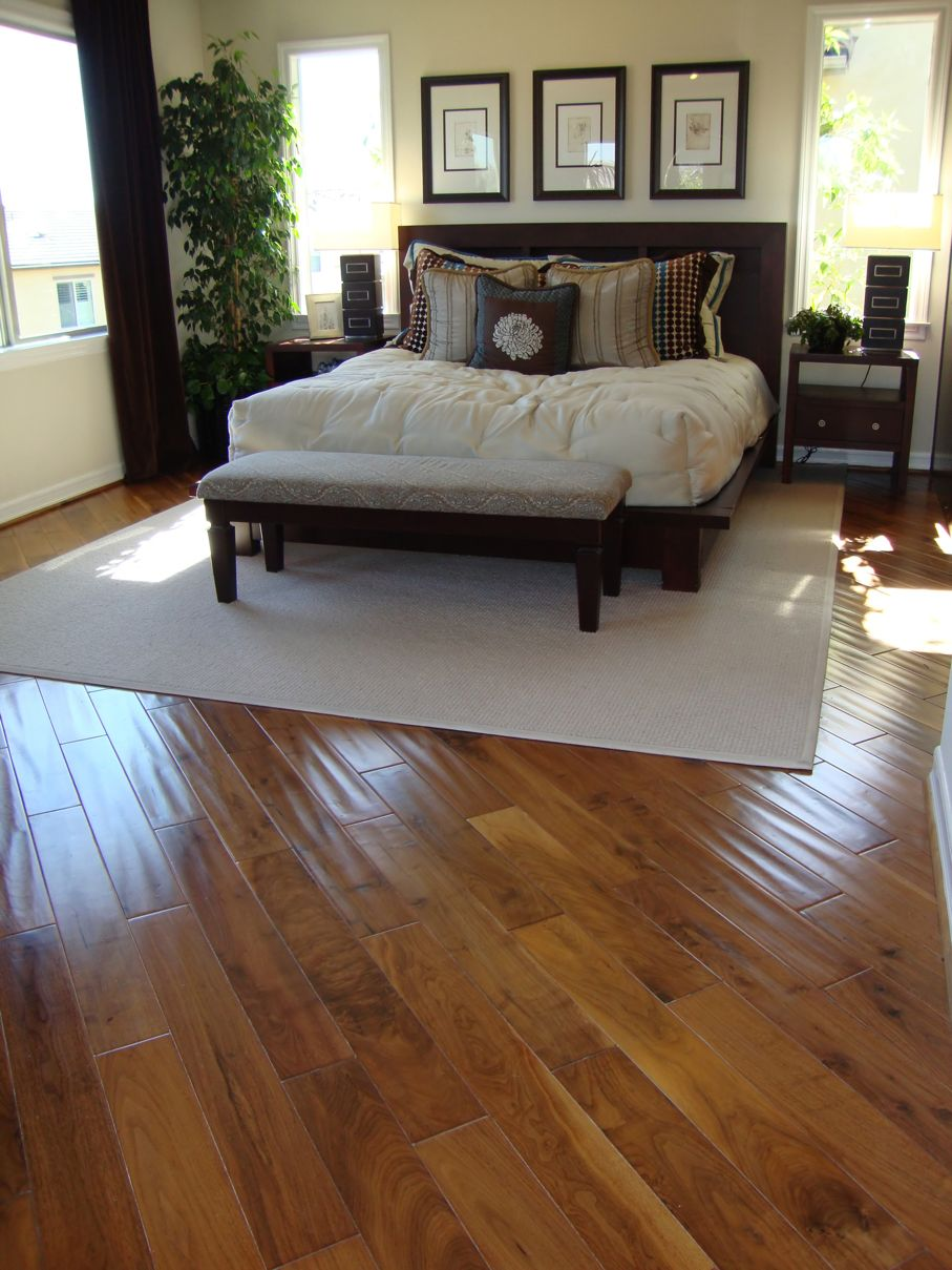 Beautiful bed room with wood floors and a rug and a bench at the foot of the bed