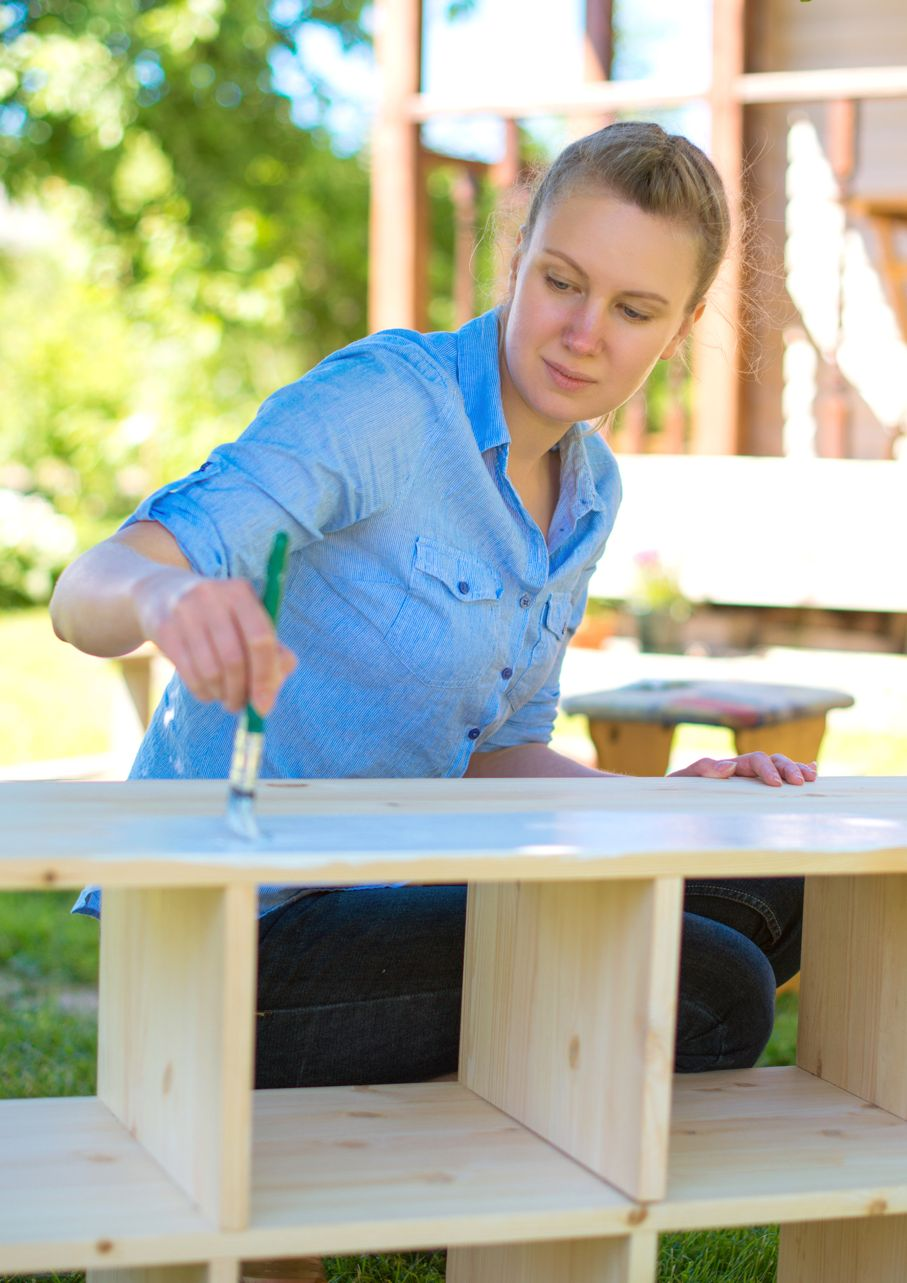 Woman with brush painting wooden furniture