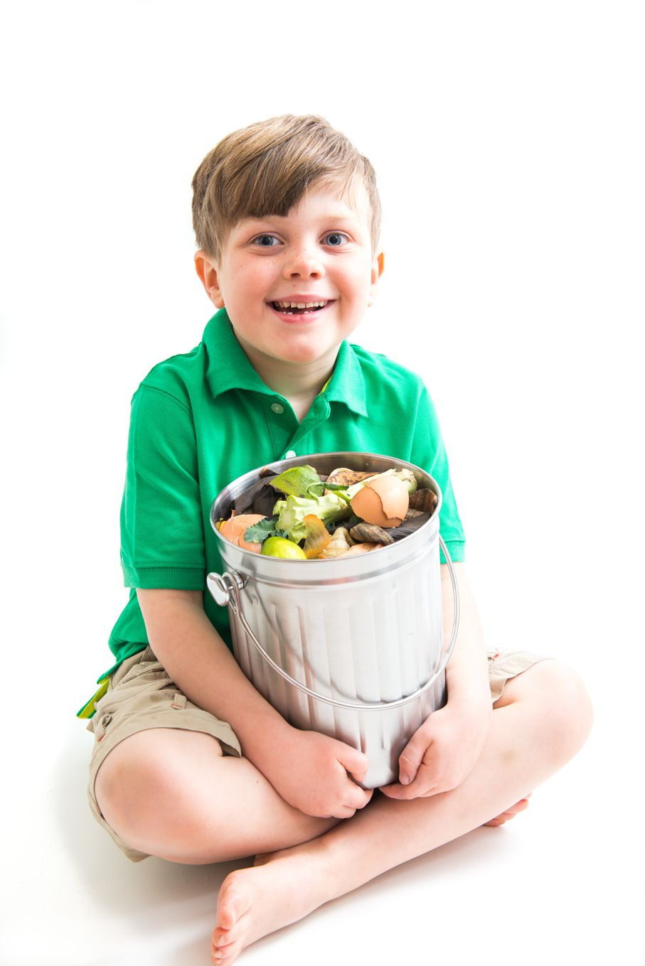Cute young boy holding compost container show environmental responsibility