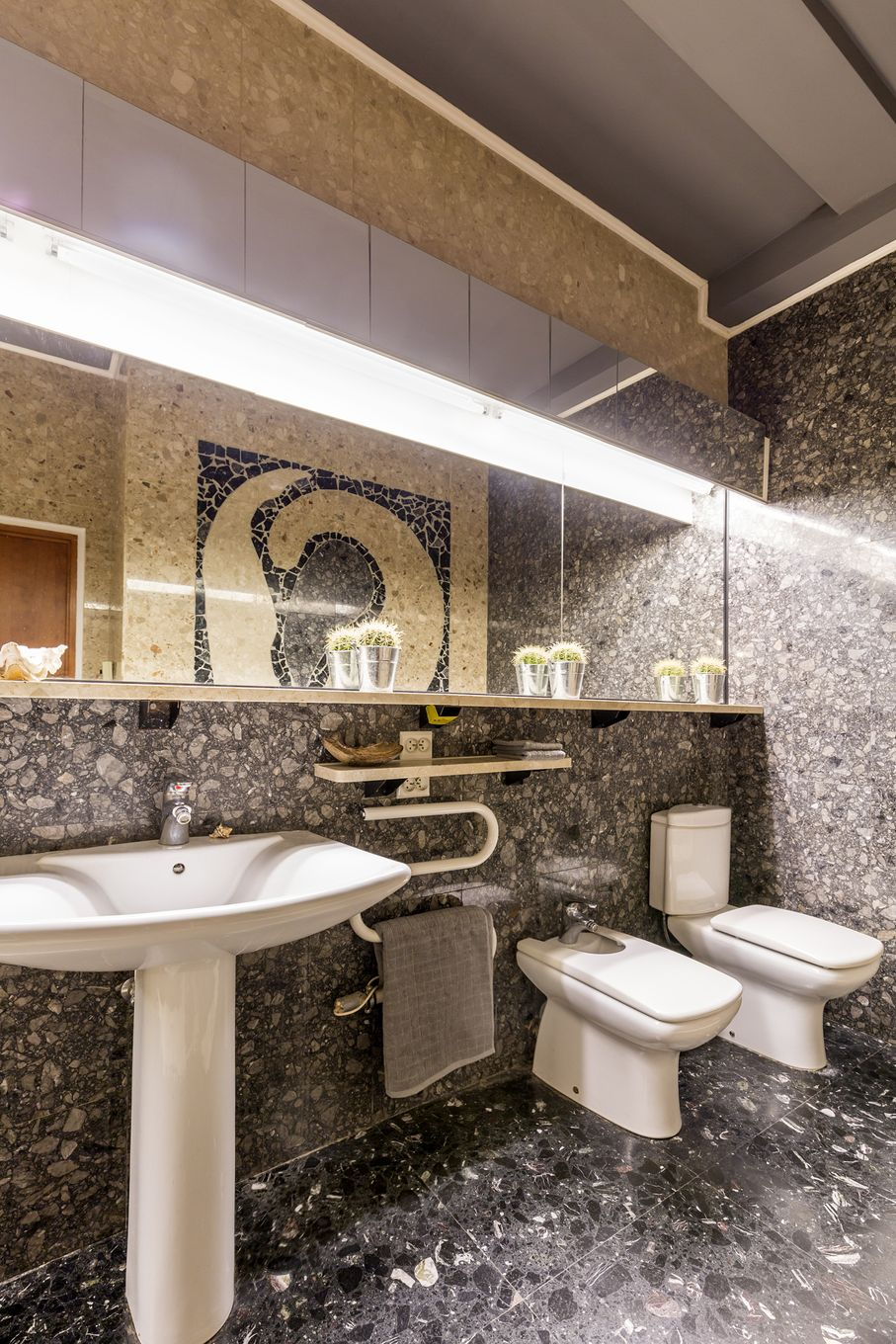 Bathroom interior with gold and grey colous with sink toilet urinalmirror mosaic on the wall and backlight