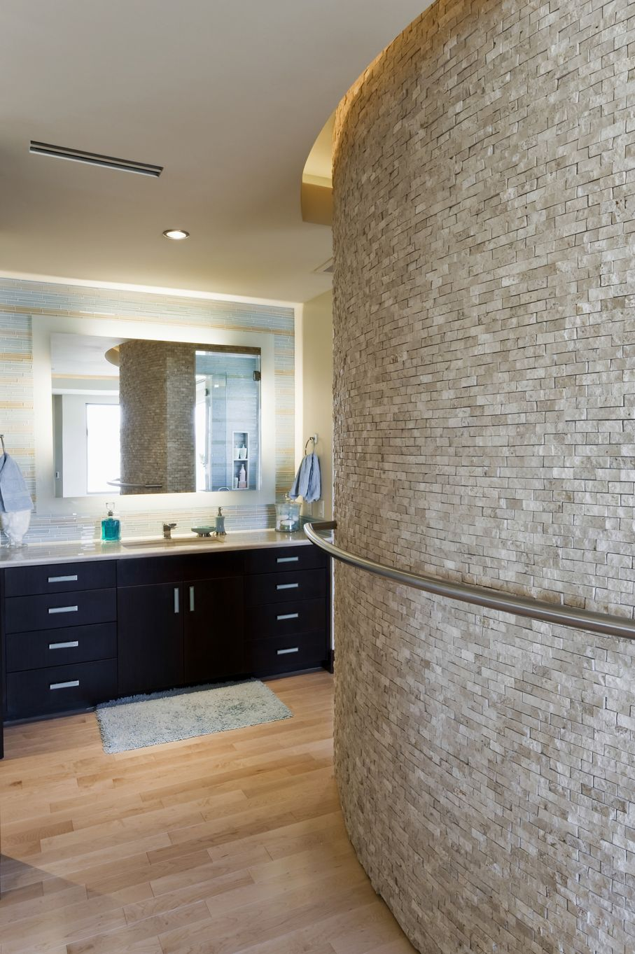 Bathroom With Curved Stone Wall And Cabinets