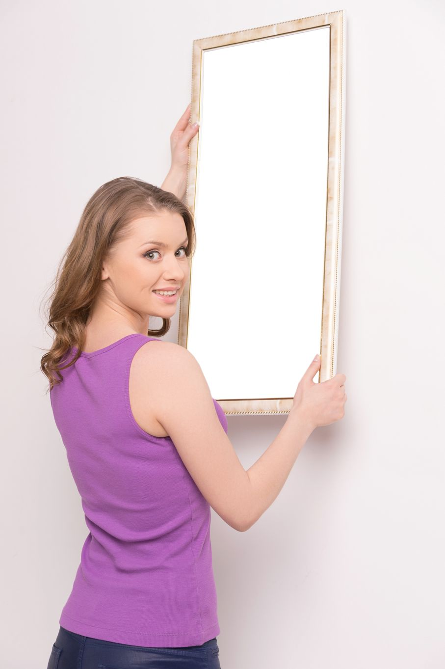 Young woman hanging mirror on wall
