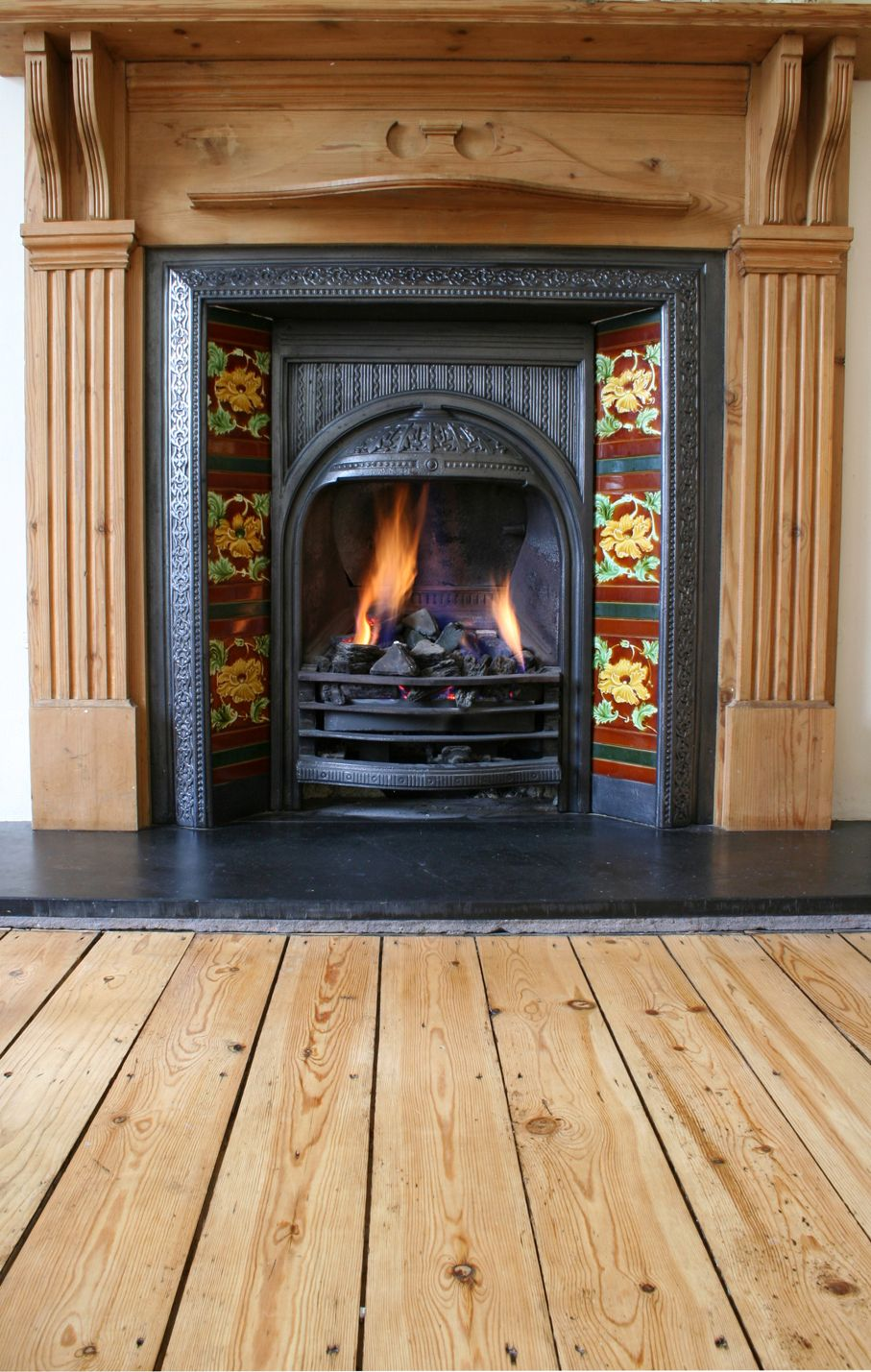 Close up of black coal fire with red floral surround and wooden mantel