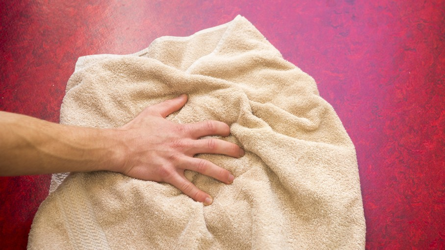 Closeup of hand and beige towel on red floor