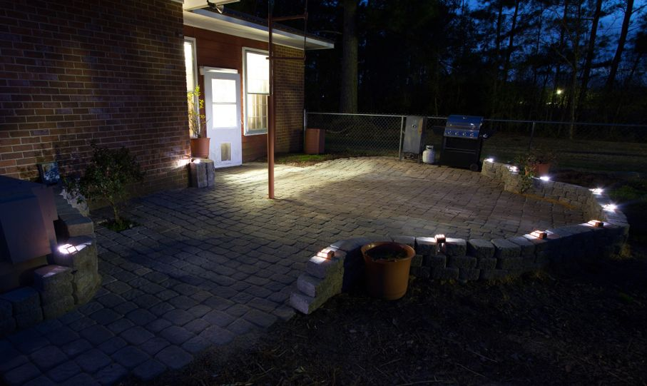 Large sand set brick patio and solar lights after nightfall