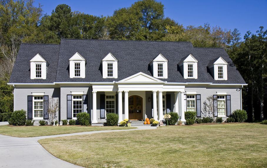A nice grey french provincial style house in the fall