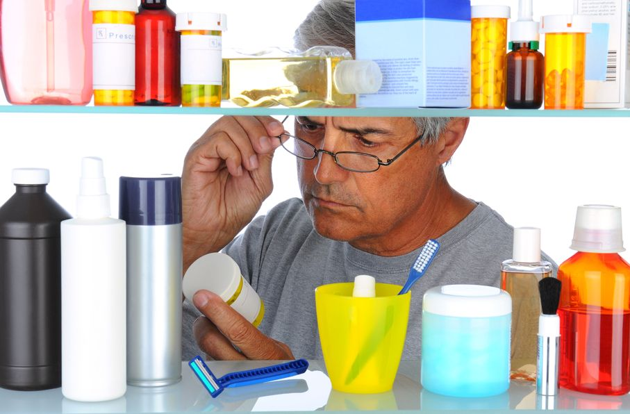 Man reading a prescription label in front of his bathroom Medicine Cabinet