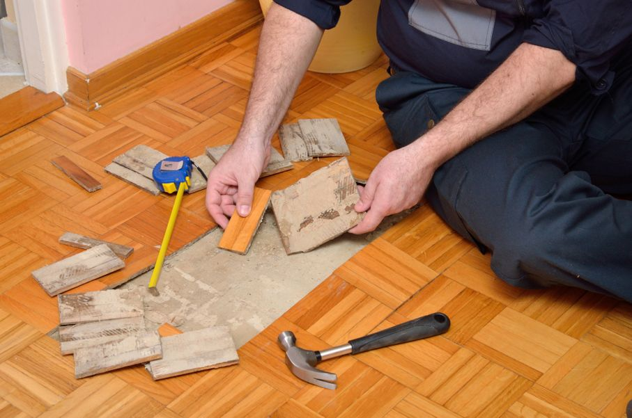 Man removing pieces of parquet damaged by moisture or water