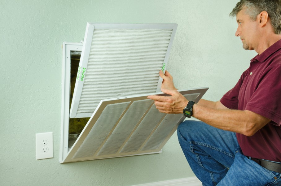 Home owner putting new air filter on air conditioner