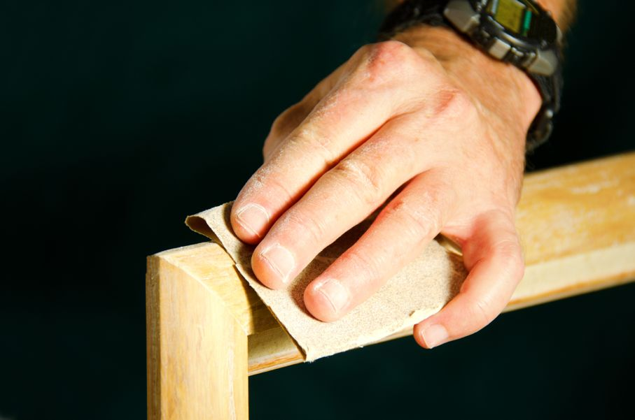 Carpenter contractor man skillfully sanding and preparing wooden molding