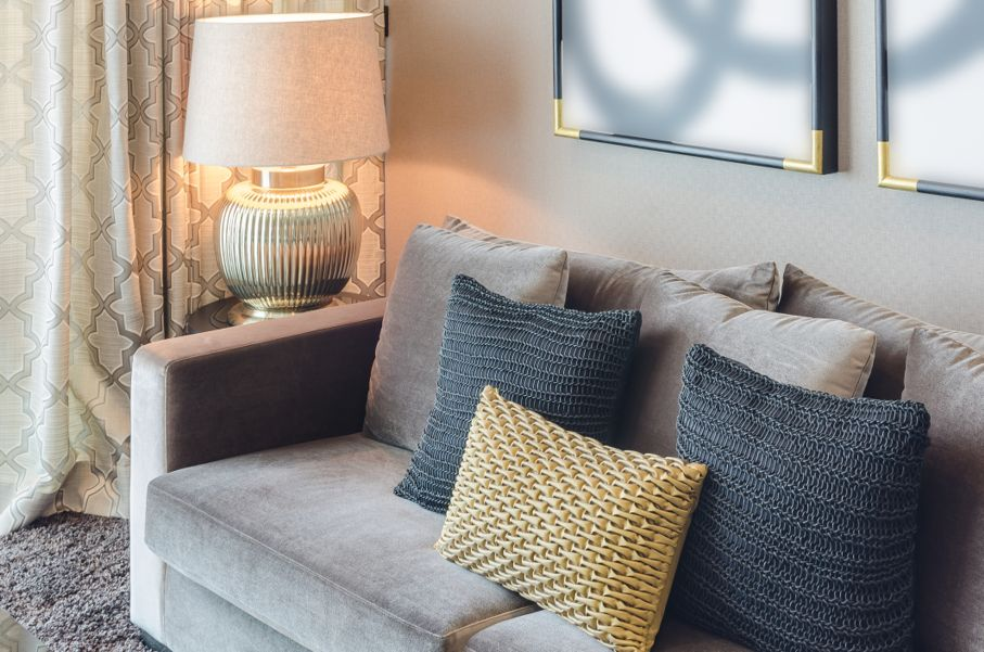 Gold and black color pillows on grey sofa
