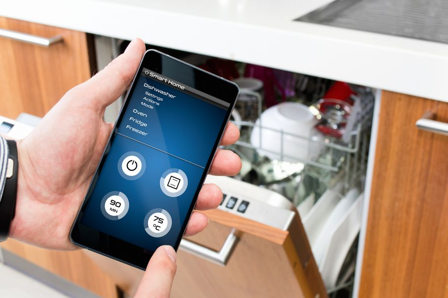 Man turns on the dishwasher by smartphone application