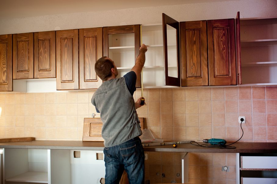 Carpenter working on new wooden kitchen cabinets