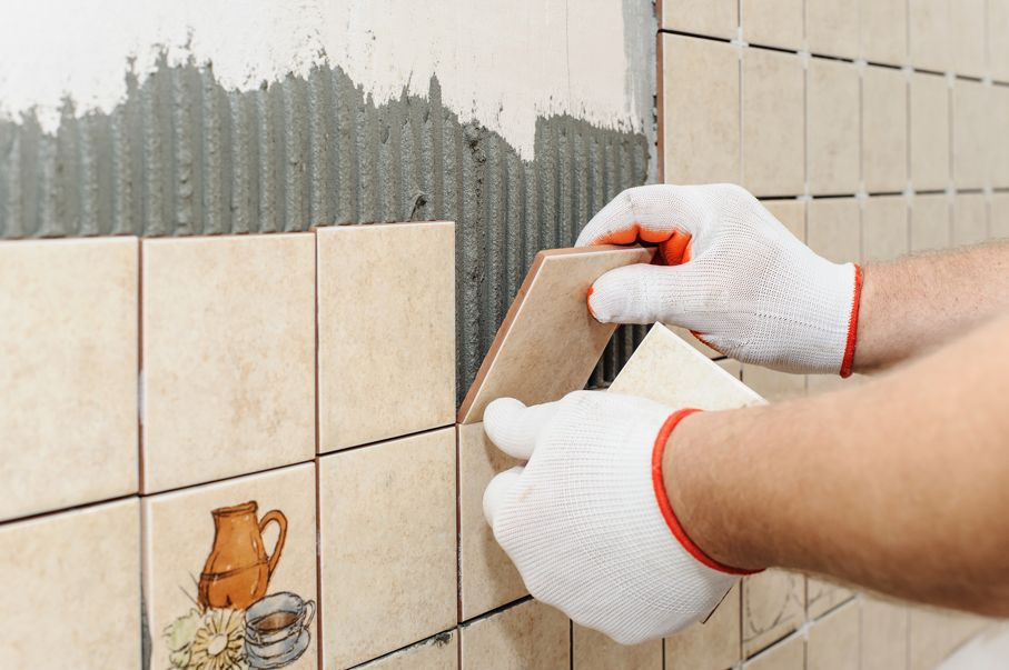 Worker sets tiles on the wall in the kitchen