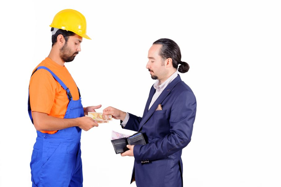 Businessman paying hired blue collar laborer for services