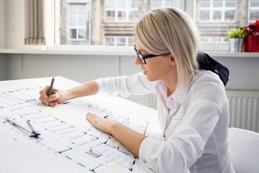 Young female architect working on architectural blueprint