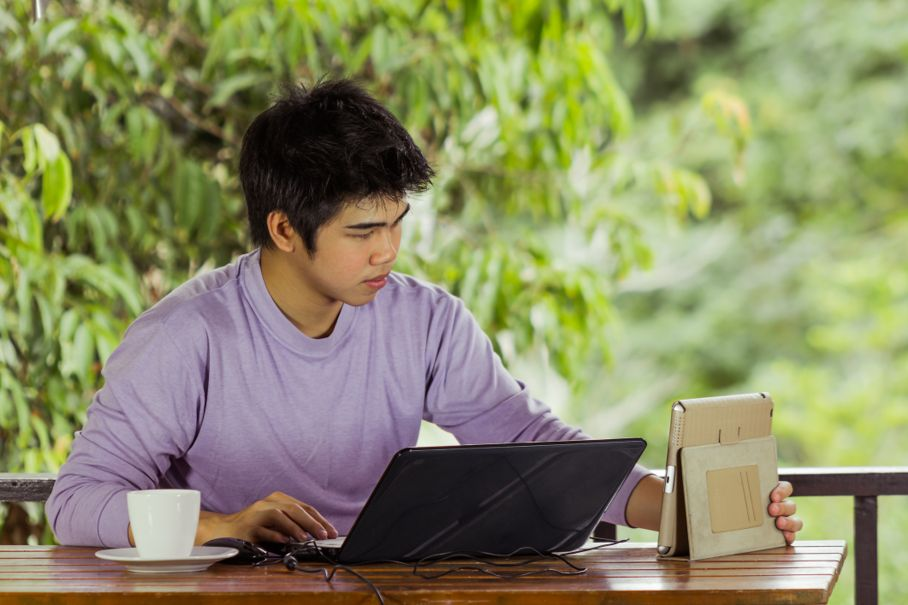 Youngman keying notebook and holding laptop
