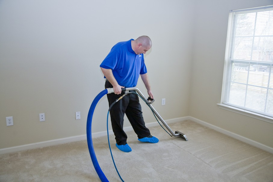 Man treating carpet with commercial cleaning chemicals to help remove stains in carpet