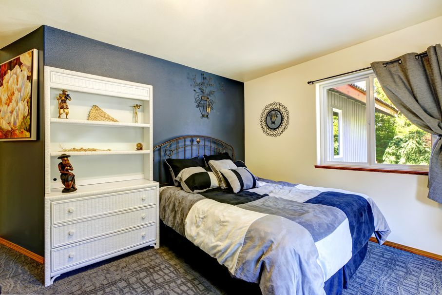 Bedroom interior with deep blue wall built-in cabinet bed with iron headboard