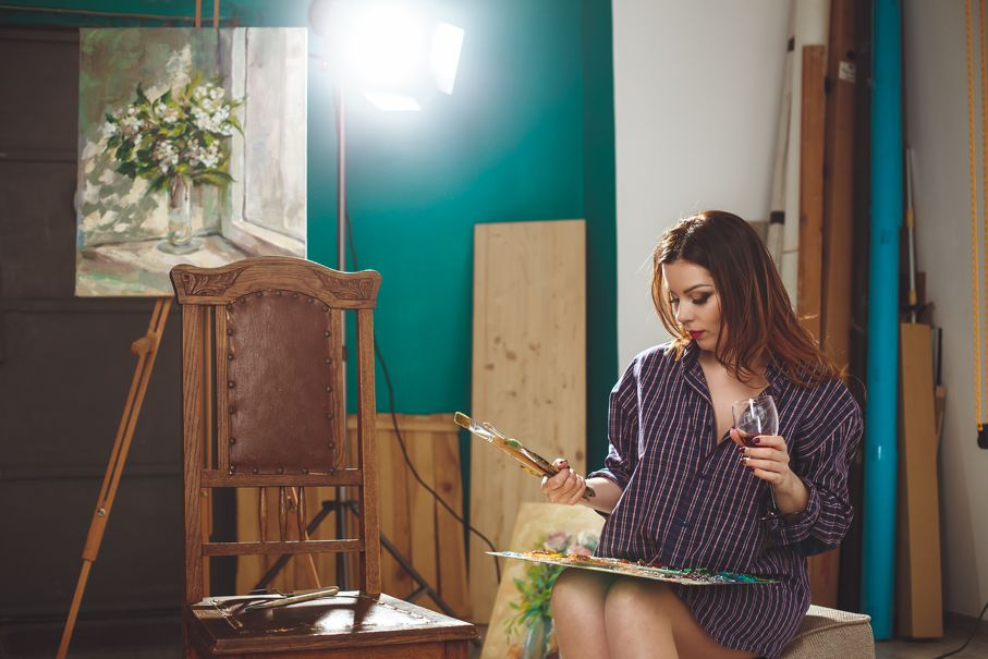 Woman artist painting a picture in loft studio