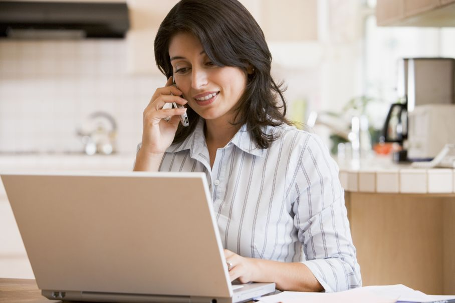 Woman in kitchen with laptop using cellular phone