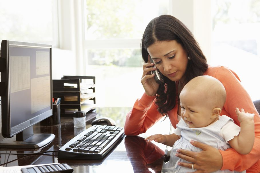 Mother with baby working in home office