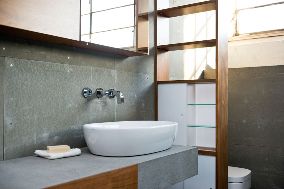 Detail of bathroom in rough concrete grey style combined with wooden parts