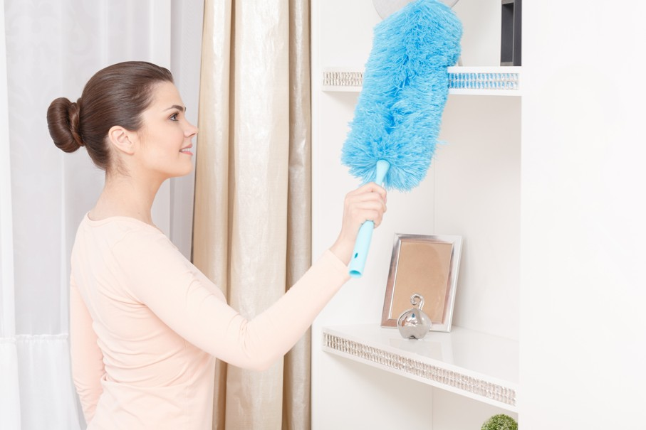 Young woman dusting shelf with the help of blue cleaning sweep