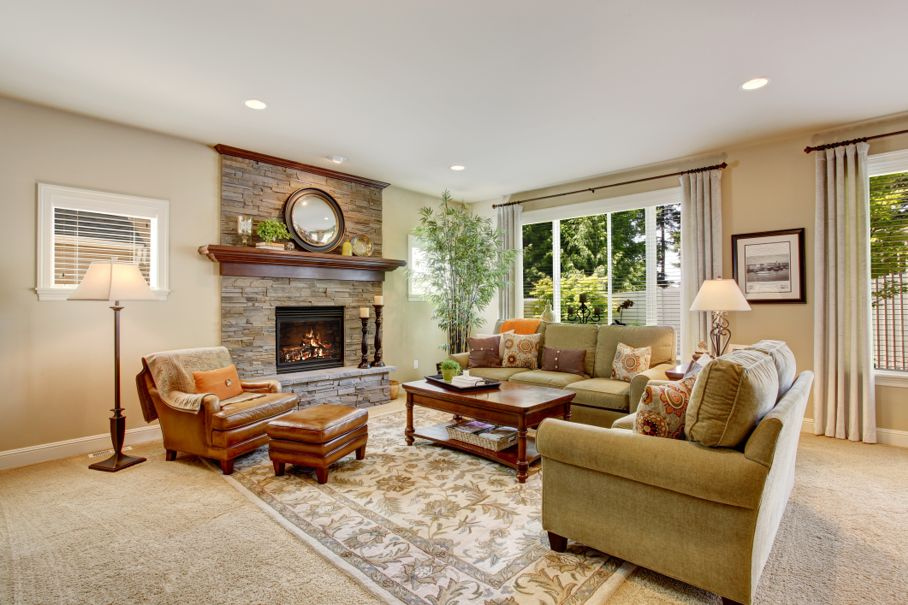 Spacious living room with fireplace, carpet floor and rug. There are two green sofas and leather brown armchair