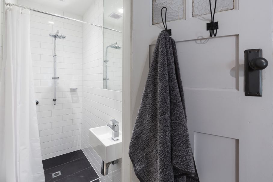 Small white tiled ensuite bathroom with shower and hanging towel on a hook horizontal
