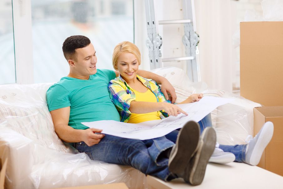 Smiling couple relaxing on sofa and looking at blueprint