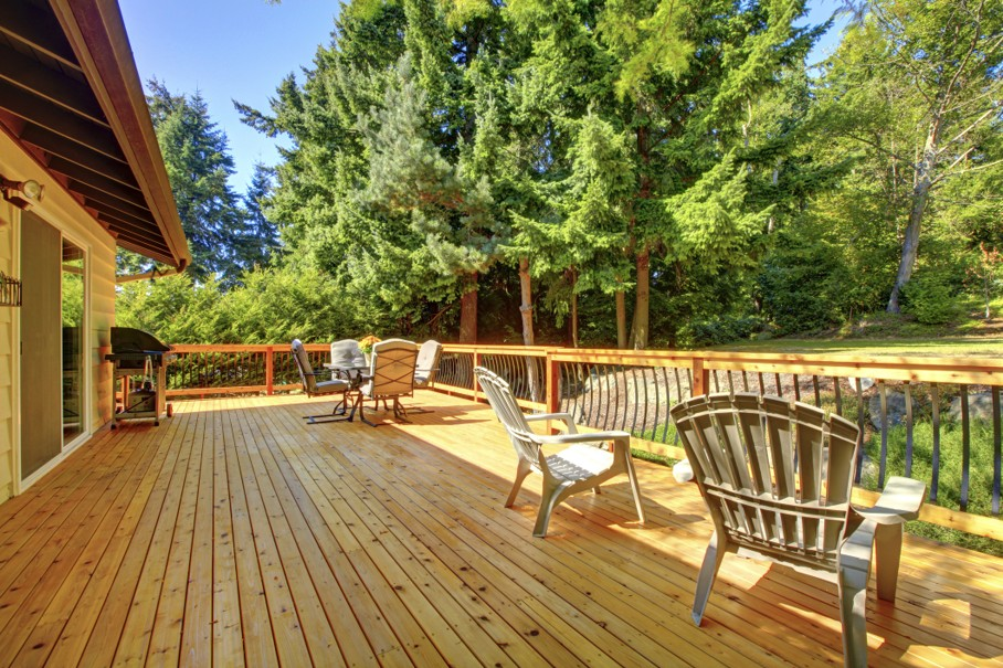 Large freshly painted new wooden deck with nice summer green backyard and outdoor furniture