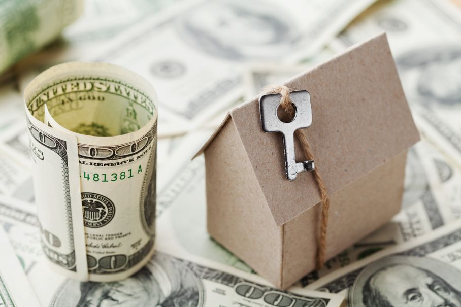 Model of cardboard home with key and dollar money