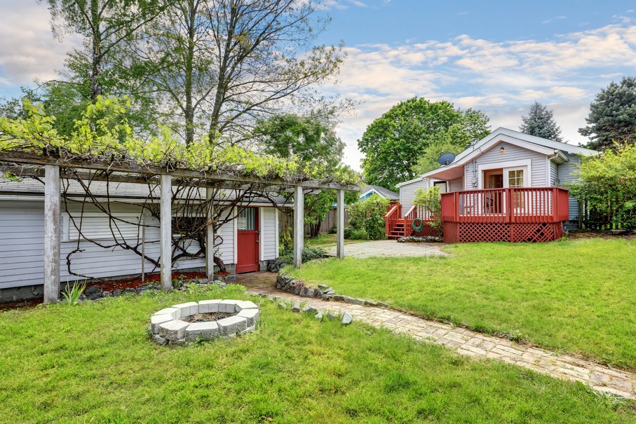 Backyard of craftsman home with red deck also a shed with grape arbor and fire pit in front