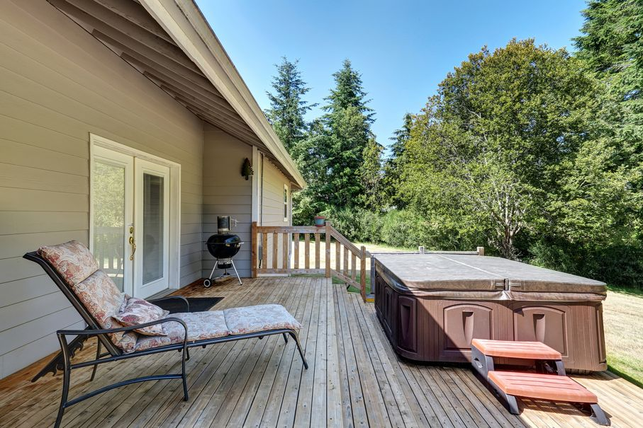 Backyard house exterior with patio area and hot tub on the walkout deck