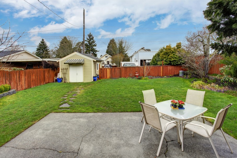 Fenced backyard with small patio area and shed