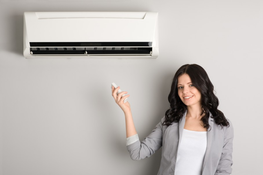 Girl holding a remote control air conditioner