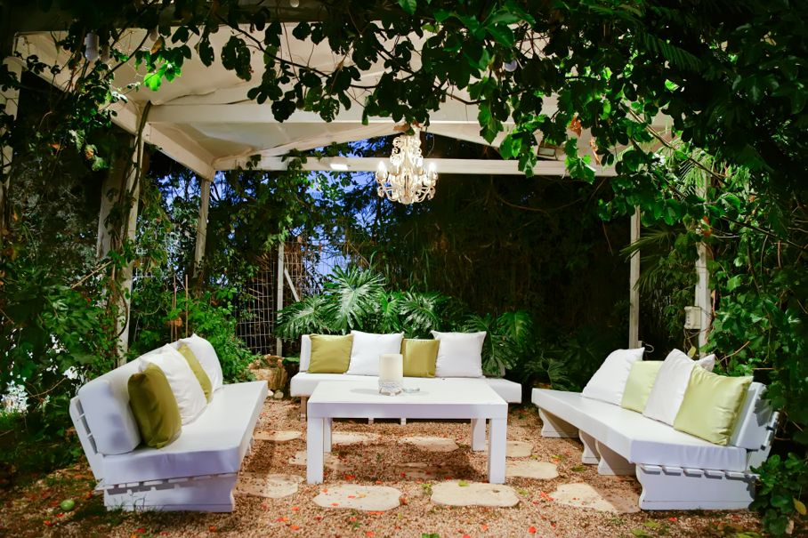 Patio in the evening with benches and pillows chandelier and table, outdoor