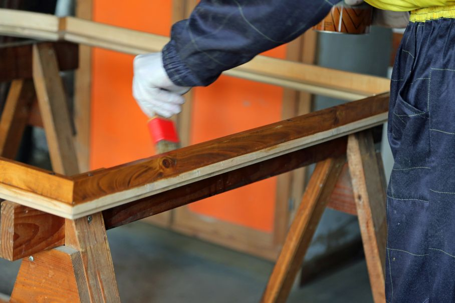 Worker during painting a wooden frame