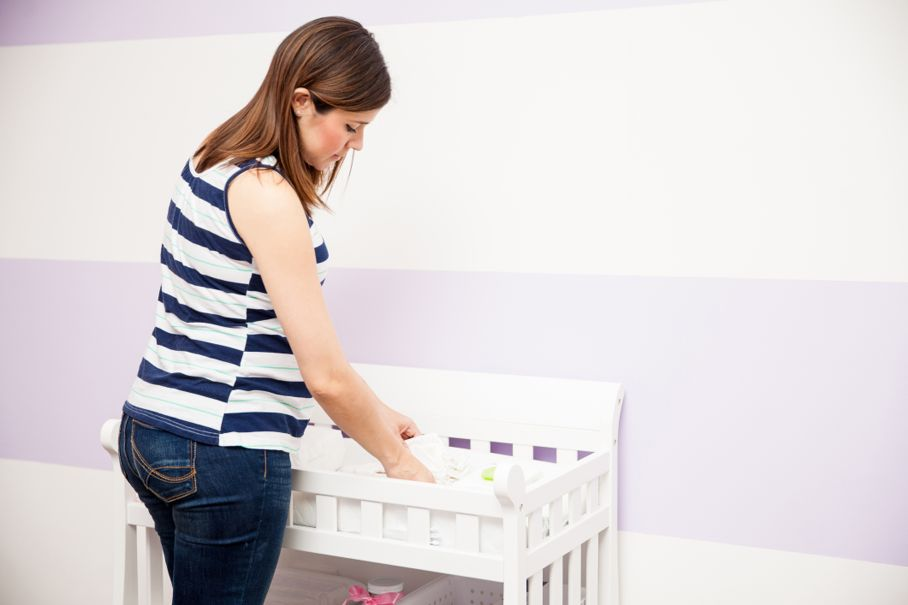 Pregnant woman storing diapers and organizing her diaper changing station in a nursery at home