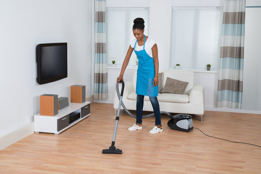 Woman Cleaning Hardwood Floor With Vacuum Cleaner