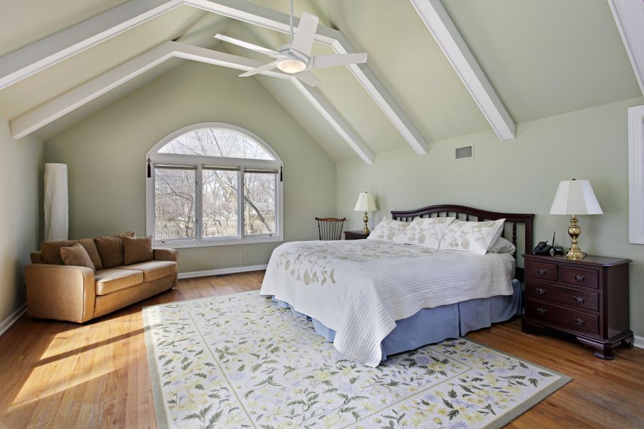 Master bedroom with ceiling beams and large window
