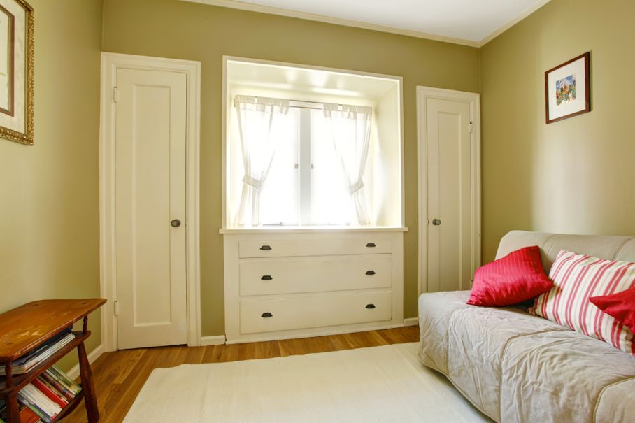 Green bedroom with white doors and dresser