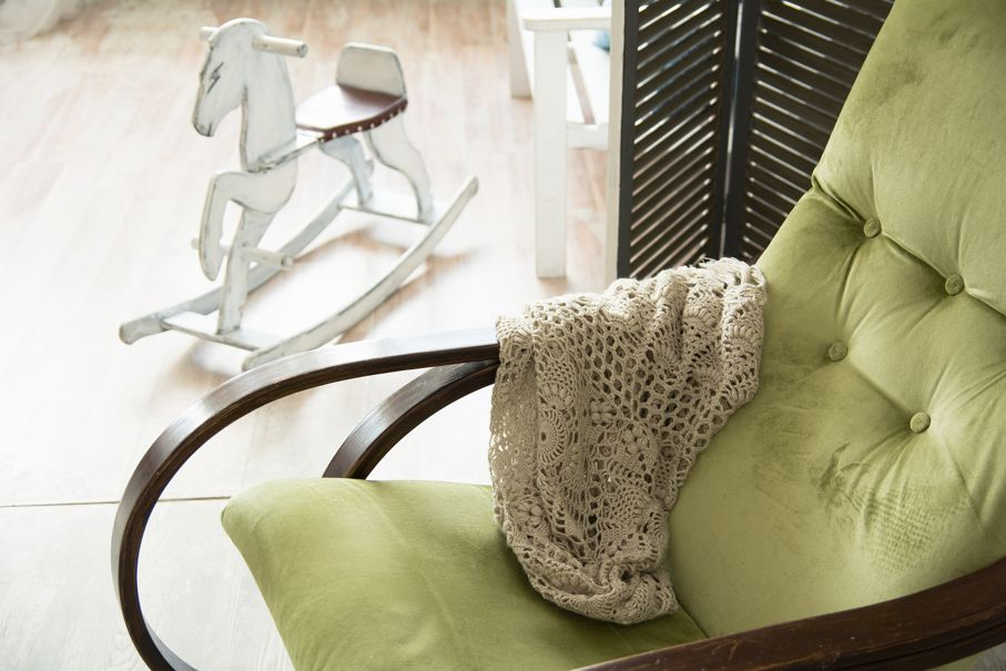 Close-up of a green rocking chair with a shawl. Children's rocking horse in the background