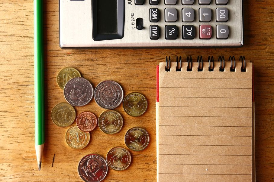 Notebook, calculator, pencil and coins
