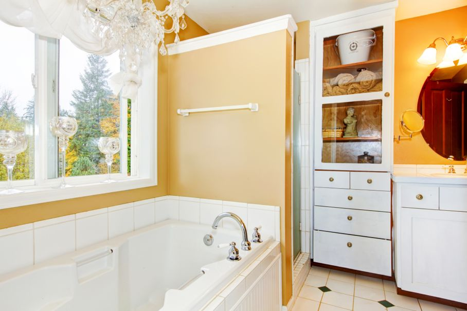Yellow bathroom with white storage combination and elegant chandelier