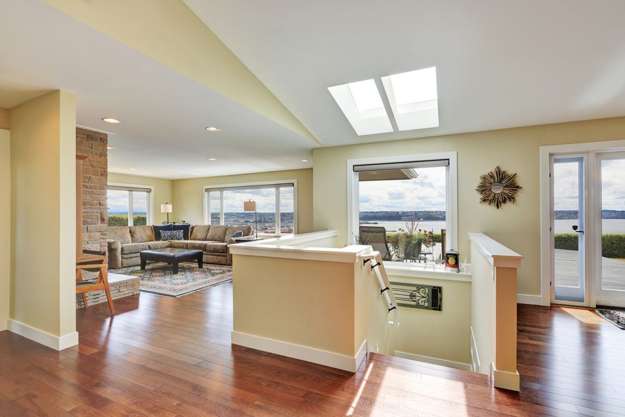 Open plan house interior with hardwood floor staircase to downstairs view of family area and vaulted ceiling with skylights