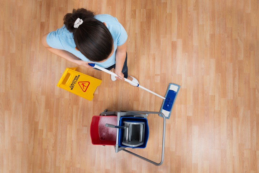 Woman With Cleaning Equipments And Wet Floor Sign Mopping Floor